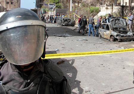 Security personnel stands guard during forensics team investigation of bombing in Alexandria