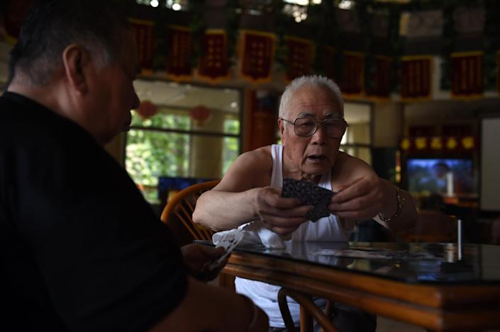 Elderly men playing cards at the Yiyangnian nursing home, a privately run aged care facility, in Beijing on June 30, 2014 (AFP Photo/Greg Baker)
