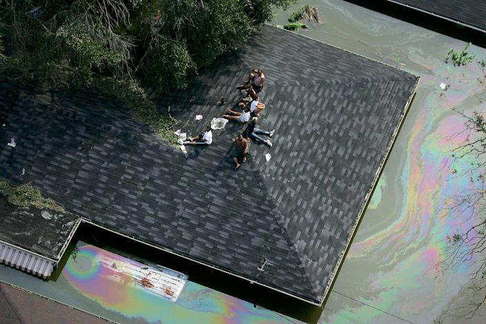 <p>People are stranded on a roof due to flood waters from Hurricane Katrina in New Orleans, La., Aug. 30, 2005. It is estimated that 80 percent of New Orleans is under flood waters as levees begin to break and leak around Lake Ponchartrain. (Vincent Laforet/AFP PHOTO/POOL/Getty Images) </p>