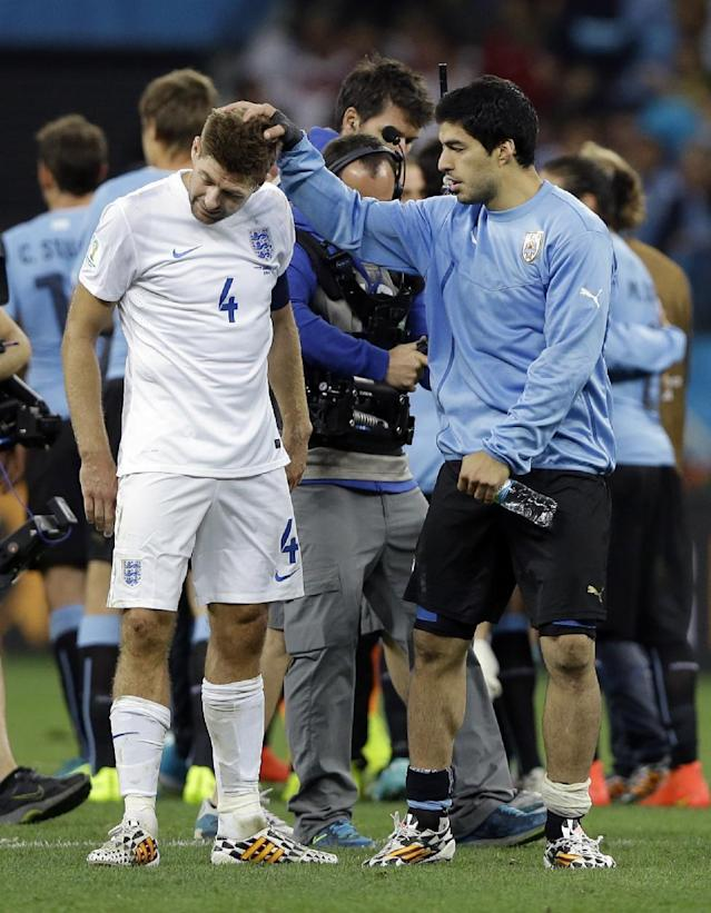 FILE - In this Thursday, June 19, 2014 file photo, Uruguay's Luis Suarez consoles England's Steven Gerrard after Uruguay's 2-1 victory over England during the group D World Cup soccer match between Uruguay and England at the Itaquerao Stadium in Sao Paulo, Brazil. England captain Steven Gerrard announced his retirement from international football on Monday, July 21, 2014. The 34-year-old Liverpool midfielder made 114 appearances for England over 14 years. (AP Photo/Kirsty Wigglesworth, File)