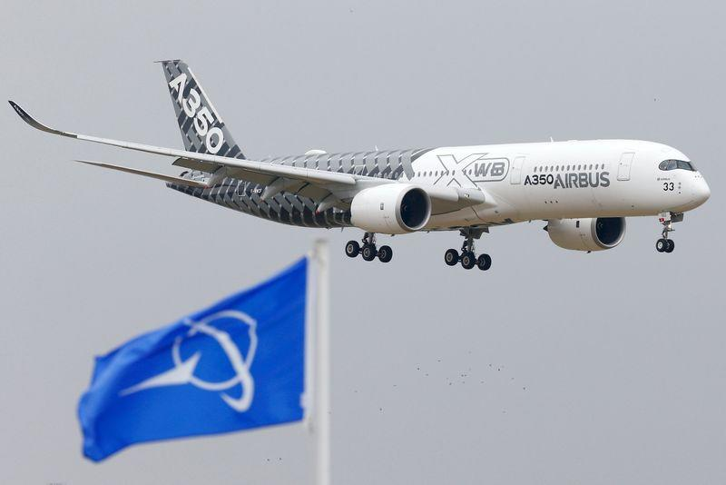 An Airbus A350 jetliner flies over Boeing flags as it lands after a flying display during the 51st Paris Air Show at Le Bourget airport near Paris