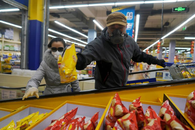 Customer in protective mask grabs potato chips while riding an escalator inside a supermarket, as the country is hit by an outbreak of the novel coronavirus, in Beijing