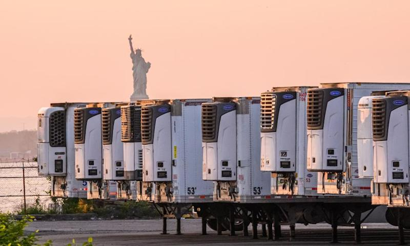 The Statue of Liberty is seen behind refrigeration trucks that function as temporary morgues at the South Brooklyn Marine Terminal during the coronavirus pandemic on May 25, 2020 in New York City.