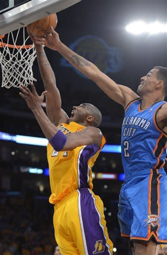 Los Angeles Lakers guard Kobe Bryant, left, puts up a shot as Oklahoma City Thunder guard Thabo Sefolosha of Switzerland defends during the first half in Game 3 of an NBA basketball playoffs Western Conference semifinal, Friday, May 18, 2012, in Los Angeles. (AP Photo/Mark J. Terrill)