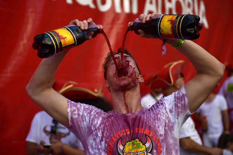 Revellers drink wine as they start celebrating early while waiting for the launch of the 'Chupinazo' rocket, to celebrate the official opening of the 2019 San Fermin fiestas with daily bull runs, bullfights, music and dancing in Pamplona, Spain, July 6, 2019. (Photo: Alvaro Barrientos/AP)