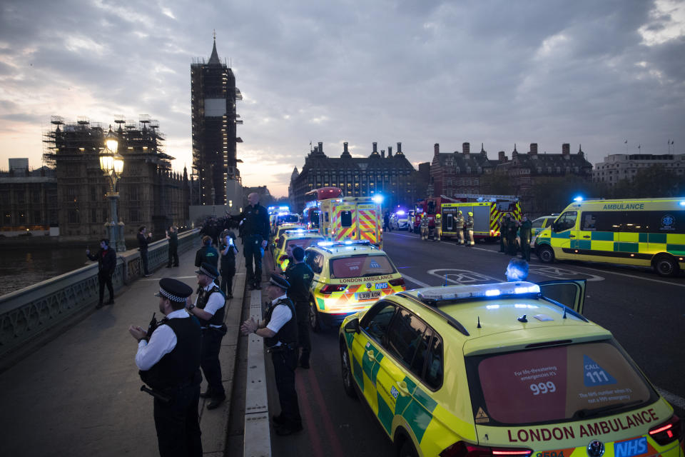 """London Ambulance staff, police officers and firefighters take part in the weekly """"clap for our carers"""" as they stand on Westminster Bridge backdropped by a scaffolded Big Ben and the Houses of Parliament in London, during the lockdown to try and stop the spread of coronavirus, Thursday, April 16, 2020. The applause takes place across Britain every Thursday at 8pm local time to show appreciation for healthcare workers, emergency services, armed services, delivery drivers, shop workers, teachers, waste collectors, manufacturers, postal workers, cleaners, vets, engineers and all those helping people with coronavirus and keeping the country functioning while most people stay at home in the lockdown. (AP Photo/Matt Dunham)"""