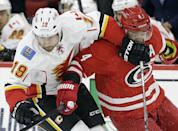 Calgary Flames' David Jones (19) and Carolina Hurricanes' Andrej Sekera (4), of Slovakia, chase the puck during the first period of an NHL hockey game in Raleigh, N.C., Monday, Nov. 10, 2014. (AP Photo/Gerry Broome)