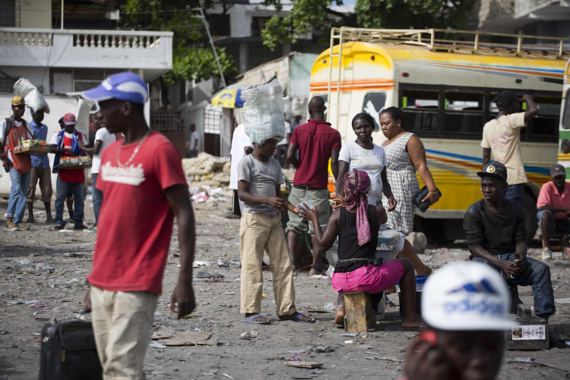 In this May 23, 2017 photo, 12-year-old Watson Saint Fleur sells water to a street vendor in Petion-Ville, a suburb of Port-au-Prince, Haiti. Watson lives with woman who took him in as an unpaid servant. Before going to work Watson bathes the woman's 7-year-old boy to prepare him for the local school he's never attended. (AP Photo/Dieu Nalio Chery)
