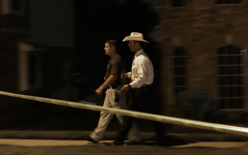 Law enforcement officers walk the scene of a fatal shooting early Thursday morning, Aug. 8, 2013, in DeSoto, Texas. Four people were killed at two different locations in South Dallas County and the suspected shooter is in police custody. (AP Photo/LM Otero)