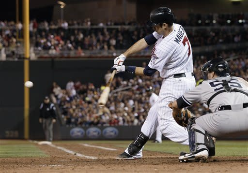 Minnesota Twins' Joe Mauer hits an RBI single in the seventh inning of a baseball game, as the Twins came from behind to beat the New York Yankees 5-4 in a baseball game Tuesday, Sept. 25, 2012 in Minneapolis. At right is Yankees catcher Russell Martin who had a solo home run in the game. (AP Photo/Jim Mone)