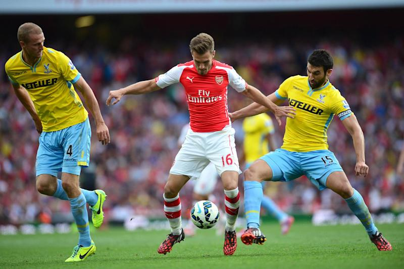 Arsenal's Aaron Ramsey (C) fights for the ball with Crystal Palace''s Brede Hangeland (L) and Mile Jedinak during their English Premier League match, at The Emirates Stadium in north London, on August 16, 2014 (AFP Photo/Carl Court)