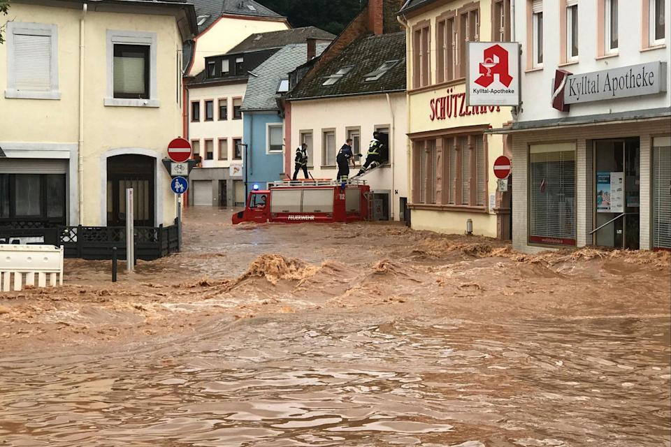 Firefighters standing on the roof of their vehicle climb into an inundatetd house in the flooded Ehrang neighbourhood in Trier, western Germany, (Fire Brigades City of Trier/AFP)