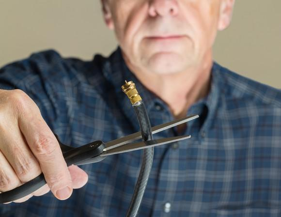 A man is taking a pair of scissors to a cable cord.