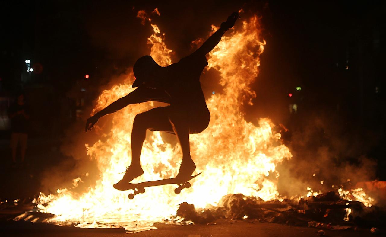 <p>A young man skateboars move in front of a fire set by protesters following a demonstration against proposed federal government reforms, March 15, 2017, in Rio de Janeiro, Brazil. Critics say the changes would reduce job security for Brazilian workers and the pension proposal would force many people to work longer to qualify for pensions and reduce retirement benefits for many. (Mario Tama/Getty Images) </p>