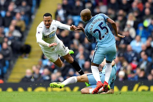 <p>Swansea City's Martin Olson is tackled by Manchester City's Pablo Zabaleta (right) and Manchester City's Fernandinho during the Premier League match between Manchester City and Swansea City at the Etihad Stadium on February 5, Manchester, England. </p>