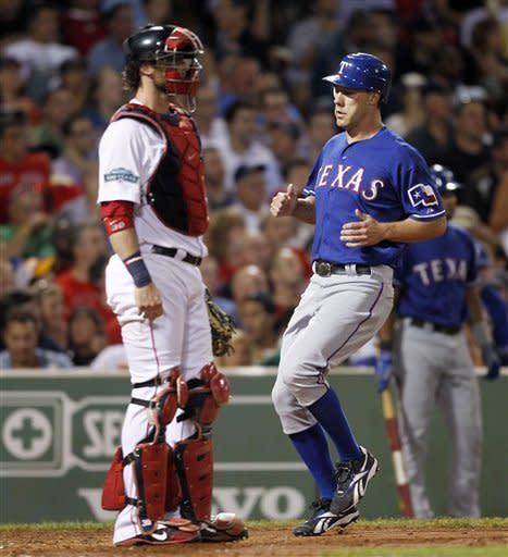 Texas Rangers' David Murphy, right, scores beside Boston Red Sox's Jarrod Saltalamacchia on a single by Ian Kinsler in the sixth inning of a baseball game in Boston, Tuesday, Aug. 7, 2012. (AP Photo/Michael Dwyer)