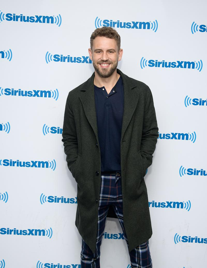 Nick Viall looks fashionable in blue pant and T-shirt, with a black coat, and the smile on his face is beautiful