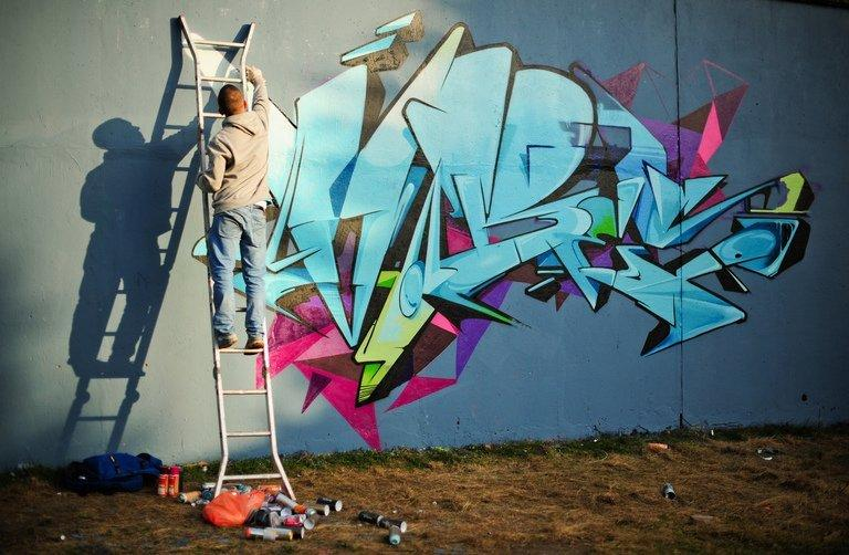 A street artist works on a new piece on a section of wall near Westbourne Park in north London on March 10, 2012