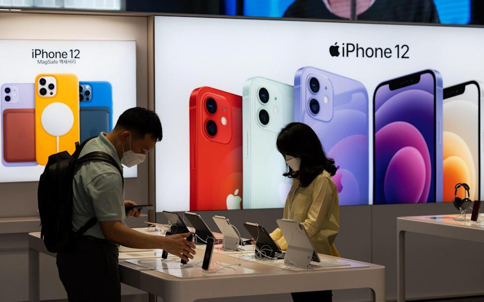 Visitors look at Apple iPhones and iPads on display in Seoul, South Korea - SeongJoon Cho/Bloomberg