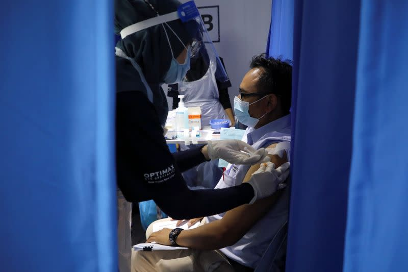 Construction worker receives a dose of the Sinovac vaccine against the COVID-19, in Kuala Lumpur