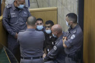 Zakaria Zubeidi, one of the six Palestinians who escaped from a high-security prison earlier this week is surrounded by guards as they stand in a courtroom in Nazareth, Israel, after he and three other Palestinian fugitives were captured on Saturday, Sept. 11, 2021. Israeli police on Saturday said they have arrested four of the six Palestinians who broke out of a maximum-security prison this week including Zubeidi a famed militant leader whose exploits over the years have made him a well-known figure in Israel. (AP Photo/Sebastian Scheiner)