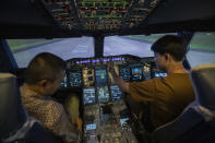 Customers sit in a Boeing A380 flight simulator during a flight experience at the Thai Airways head office in Bangkok, Thailand on Oct. 3, 2020. The airline is selling time on its flight simulators to wannabe pilots while its catering division is serving meals in a flight-themed restaurant complete with airline seats and attentive cabin crew. The airline is trying to boost staff morale, polish its image and bring in a few pennies, even as it juggles preparing to resume international flights while devising a business reorganization plan. (AP Photo/Sakchai Lalit)