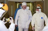 FILE In this file pool photo taken on Friday, Nov. 27, 2020, Belarusian President Alexander Lukashenko, center, listens to medic official as he visits the hospital for coronavirus patients in Minsk, Belarus. A wave of COVID-19 has spread through Belarusian jails packed with people imprisoned for taking part in four months of protests against the nation's authoritarian president. Activists, who tested positive after being released, describe massively overcrowded cells and the lack of basic amenities, and some even allege that the authorities have deliberately spread contagion among political prisoners. (Andrei Stasevich/BelTA Pool Photo via AP, File)