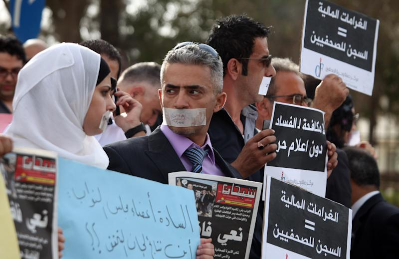 "FILE --  In this Thursday Sept. 29, 2011 file photo, Jordanian journalists protest in front the Jordanian House of Parliament, symbolically wearing tape over their mouths, as they protest over proposed changes to the anti-corruption law they believe will muzzle press freedoms, in Amman, Jordan. Jordan's prime minister Abdullah Ensour told a meeting of the Geneva-based International Press Institute (IPI) that Jordan has ""come a long way"" in improving both legislation governing press freedoms and the standards of a national media still reeling under long years of state censorship. Nidal Mansour, head of the Amman-based Center for Defending Freedom of Journalists --IPI's hosting partner -- said that the press law enacted last year was designed to muzzle press freedoms. (AP Photo/Mohammad Hannon, File)"