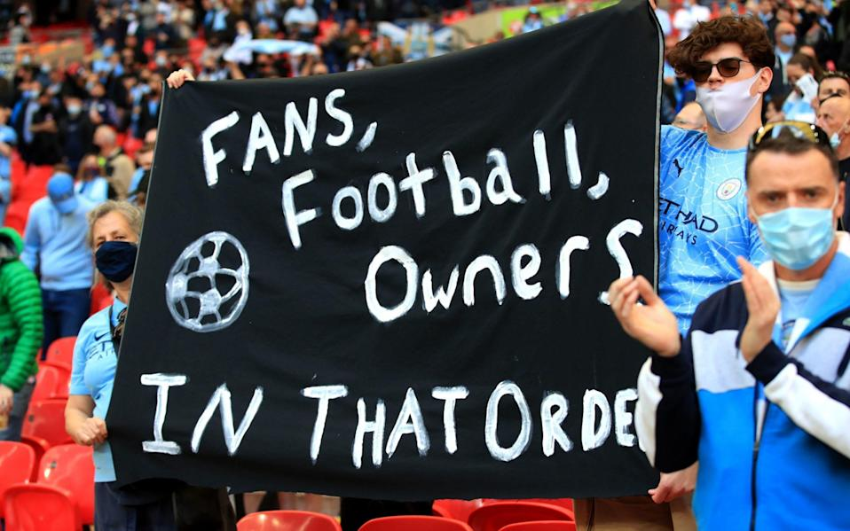 Fans hold banner protesting owners.