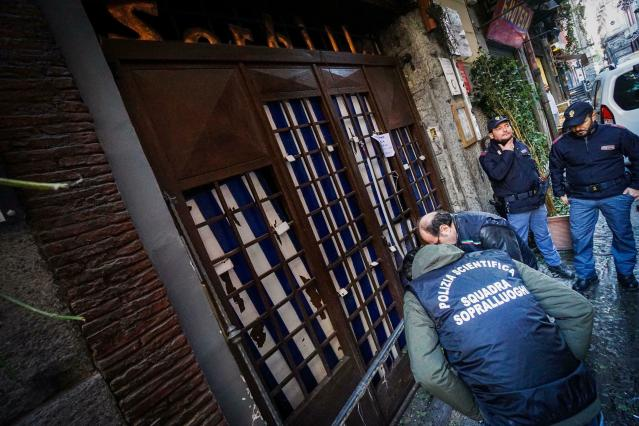 Police officers look at the entrance to the historic Sorbillo pizzeria, in the historic center of Naples, where a bomb was detonated in the early hours of Wednesday, Jan. 16, 2019, damaging the eatery's metal grating. The Italian news agency ANSA said eight bombs have targeted businesses in the Naples area in recent days. (Cesare Abbate/ANSA via AP)