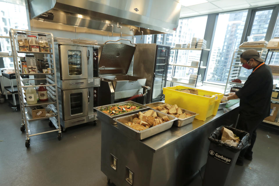 Joseph Robello, lead cook at Mary's Place, a family homeless shelter located inside an Amazon corporate building on the tech giant's Seattle campus, prepares food Wednesday, June 17, 2020. The facility is home to the Popsicle Place shelter program, an initiative to address the needs of homeless children with life-threatening health conditions. (AP Photo/Ted S. Warren)