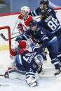 Winnipeg Jets goaltender Connor Hellebuyck (37) dives onto the rebound as Montreal Canadiens' Phillip Danault (24) crashes into him and Jets' Neal Pionk (4) defends during the second period of an NHL hockey game Saturday, Feb. 27, 2021, in Winnipeg, Manitoba. (John Woods/The Canadian Press via AP)