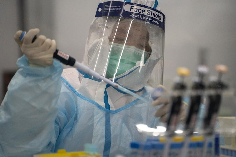 A lab technician wearing protective suit processes RT-PCR Covid-19 tests at Prenetics' laboratory in Hong Kong on Friday, July 31, 2020. Photo: Bloomberg