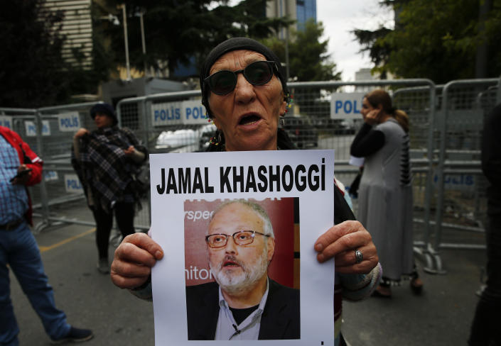An activist, member of the Human Rights Association Istanbul branch, holds a poster with a photo of missing Saudi journalist Jamal Khashoggi, during a protest in his support near the Saudi Arabia consulate in Istanbul, Tuesday, Oct. 9, 2018. Turkey said Tuesday it will search the Saudi Consulate in Istanbul as part of an investigation into the disappearance of a missing Saudi contributor to The Washington Post, a week after he vanished during a visit there. (AP Photo/Lefteris Pitarakis)
