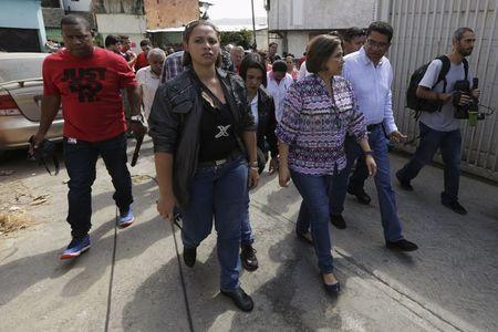 Venezuela's Health Minister Luisana Melo (front 3rd R) walks during a fumigation campaign at the Valle slum to help control the spread of the mosquito-borne Zika virus in Caracas, January 28, 2016. REUTERS/Marco Bello