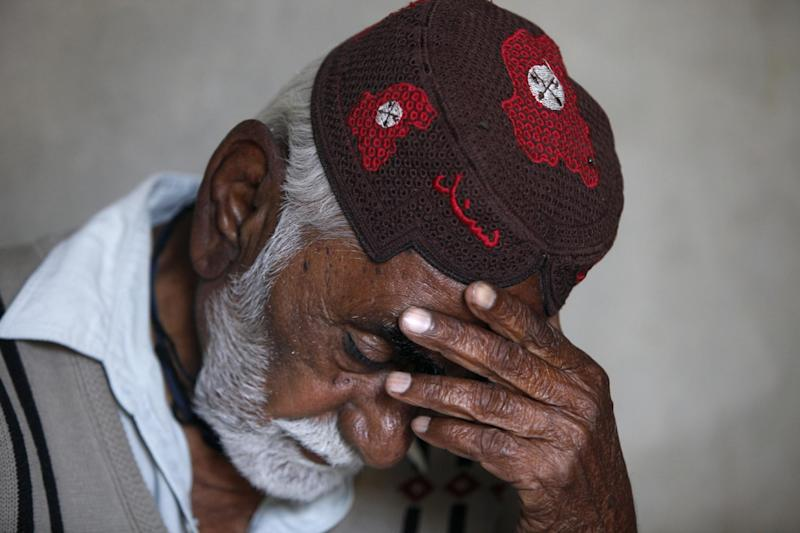 In this Wednesday, Feb. 26, 2014 photo, Pakistani Jamal Din, father of police officer Didar Ahmed, who was killed along with three other police officers in early February, reacts while talking about his son at his home in Karachi, Pakistan. The jacket that Karachi police officer Didar Ahmed was wearing when he was killed was given back to his family after his death. Bullet holes have pierced the sleeves and chest, marking where Ahmed was shot. In some areas the jacket is stained dark with dried blood. (AP Photo/Shakil Adil)