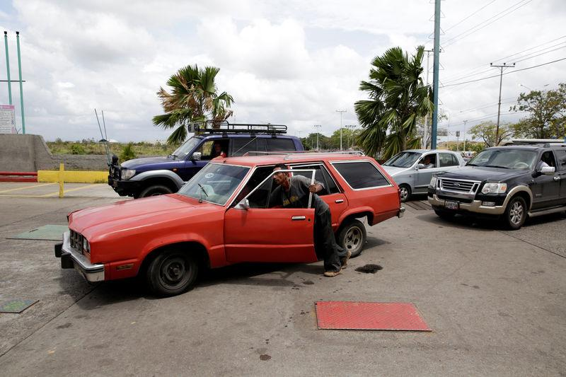 A man pushes his car after running out of gas at a gas station of Venezuelan state oil company PDVSA in Maturin