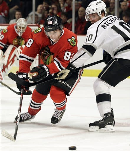 Chicago Blackhawks' Patrick Kane (88) controls the puck against Los Angeles Kings' Mike Richards (10) during the first period of an NHL hockey game in Chicago, Sunday, March 11, 2012. (AP Photo/Nam Y. Huh)