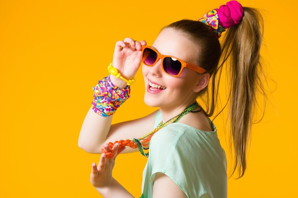 Smiling girl with colorful clothes wearing sunglasses, yellow background.