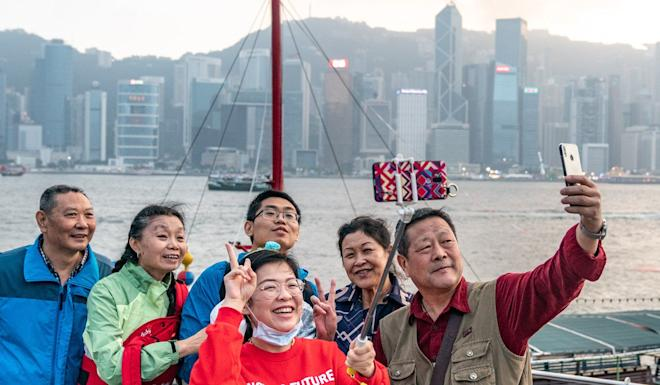 Tourists taking selfies in Victoria Harbour in Hong Kong. Photo: Bloomberg