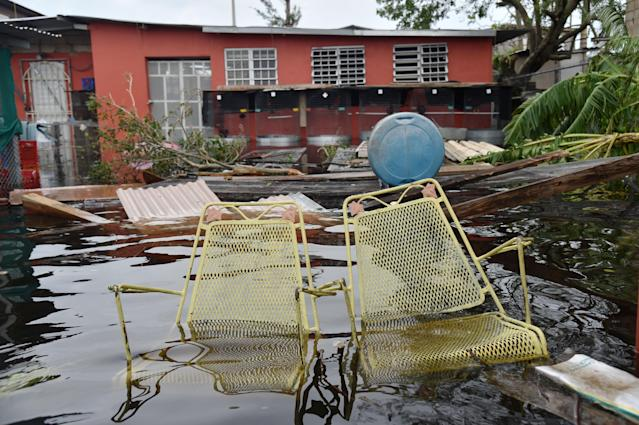 <p>Chairs are seen in front of a flooded house in Juana Matos, Catano, Puerto Rico, on Sept. 21, 2017. (Photo: Hector Retamal/AFP/Getty Images) </p>