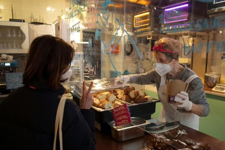 """A customer orders """"Buchteln"""", an Austrian speciality filled with marmalade, as a grandmother packs them, in the Vollpension cafe, in Vienna"""