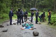A woman plays a trumpet while lying on the road as RCMP officers assemble during an operation to arrest protesters in the Fairy Creek area of Vancouver Island