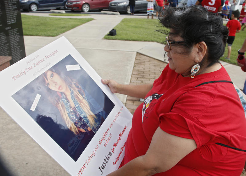 """FILE - In this Friday, June 14, 2019, file photo, Carmen Thompson, of El Reno, Okla., looks over a poster of her niece Emily Morgan who was murdered in 2016, before the start of a march to call for justice for missing and murdered indigenous women at the Cheyenne and Arapaho Tribes of Oklahoma in Concho, Okla. U.S. Senate staffers say officials missed a second deadline on July 8 to offer input on bills on Native American safety, and only one department has since provided """"partial comment."""" (AP Photo/Sue Ogrocki, File)"""