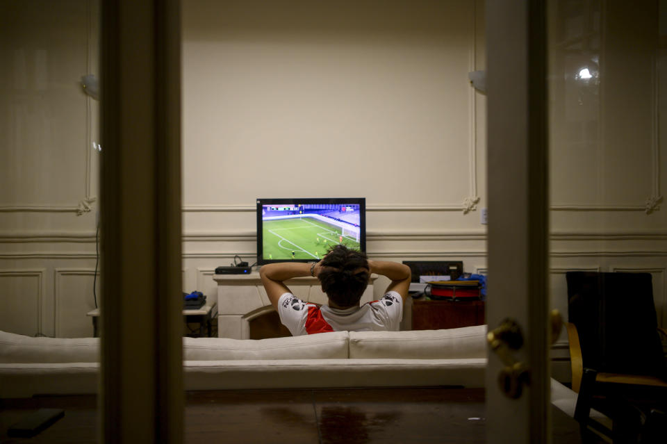River Plate soccer fan Juan Camisassa watches his team play Club Atletico Aldosivi on television at his home during COVID-19 pandemic restrictions banning fans from stadiums in Buenos Aires, Argentina, Thursday, Aug. 26, 2021. Few places in the world have soccer fans more passionate than those in Argentina, and few have been so long denied a live view of their teams due to the pandemic. (AP Photo/Mario De Fina)