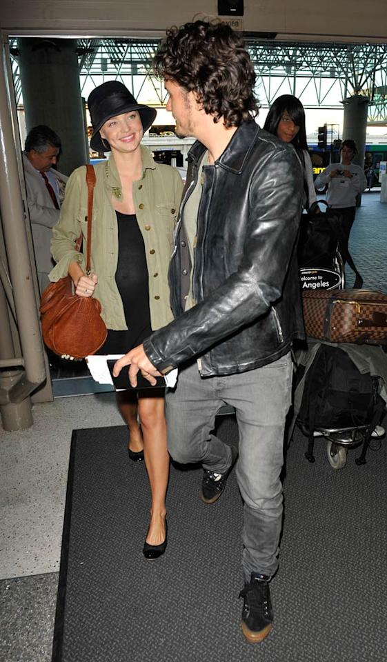 """Miranda Kerr proudly showed off her petite baby bump when she was spotted at LAX airport with her new hubby, Orlando Bloom, Thursday. The Victoria's Secret model is reportedly due around the new year. Hot Shots Worldwide/<a href=""""http://www.splashnewsonline.com"""" target=""""new"""">Splash News</a> - September 9, 2010"""