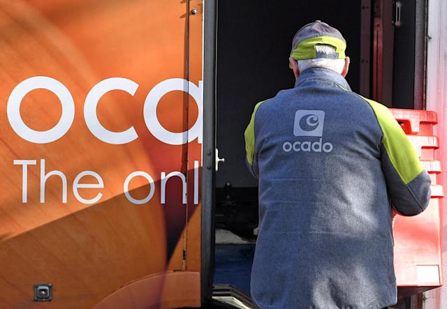 A delivery driver returns empty crates to his Ocado delivery van. (Paul Ellis/AFP via Getty Images)