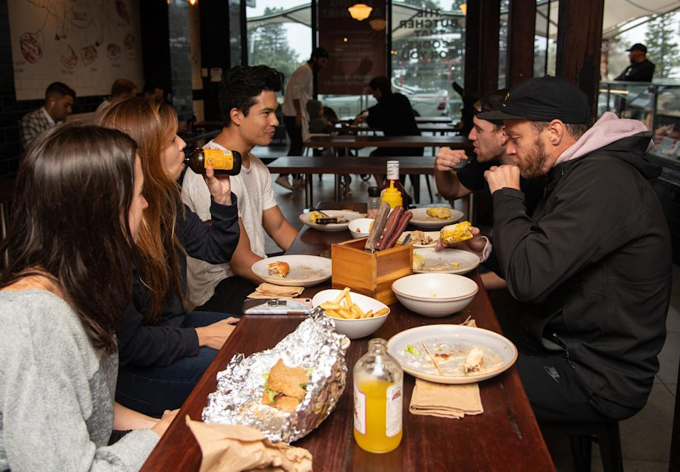 A group of people dining in at Macelleria Restaurant in Bondi Beach, Sydney.
