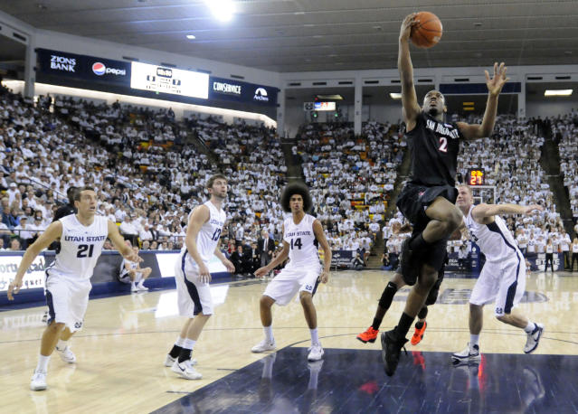 San Diego State guard Xavier Thames (2) drives to the basket as Utah State's Spencer Butterfield, from left, guard Preston Medlin, forward Jalen Moore and center Jordan Stone defend in the first half of an NCAA college basketball game Saturday, Jan. 25, 2014, in Logan, Utah. (AP Photo/Eli Lucero)