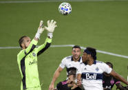Seattle Sounders goalkeeper Stefan Frei, left, grabs the ball away from Vancouver Whitecaps defender Derek Cornelius, right, during the second half of an MLS soccer match in Portland, Ore., Tuesday, Oct. 27, 2020. Seattle won 2-0. (AP Photo/Steve Dykes)